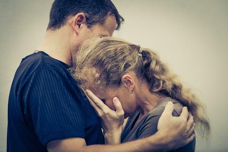 그녀의 남편을 포옹하는 슬픈 여자