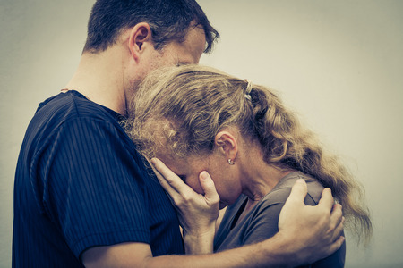 argument from love: Sad woman hugging her husband Stock Photo