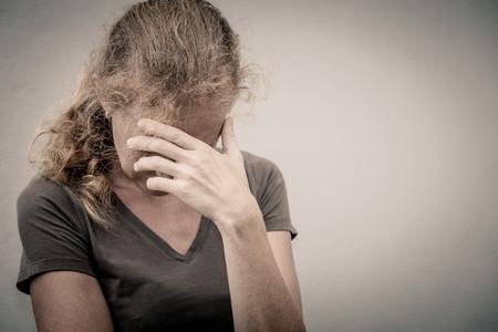 portret van een trieste vrouw stond in de buurt van een muur en houdt haar hoofd in haar handen