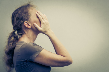 tired person: portrait of one sad woman standing near a wall and holding her head in her hands Stock Photo