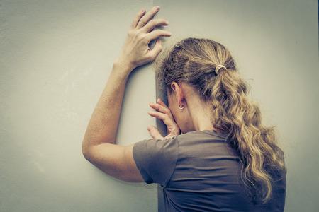 벽 근처에 서있는 한 슬픈 여자의 초상화