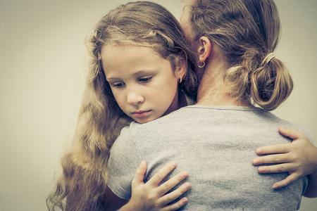 niños tristes: retrato de una hija triste abrazando a su mamá