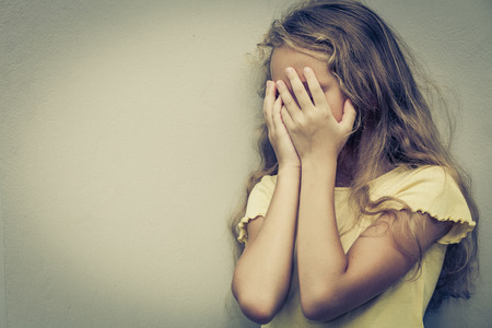 abuse young woman: Portrait of sad blond teen girl standing near wall at the day time Stock Photo