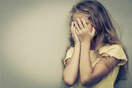 maltrato infantil: Retrato de muchacha triste adolescente rubio de pie cerca de la pared en el tiempo del d�a Foto de archivo