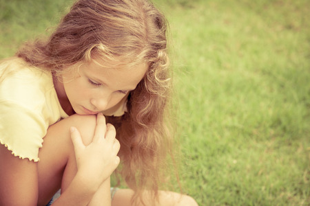 Portrait of sad blond teen girl sitting on the grass at the day time photo
