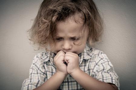 hombre solitario: Retrato del niño pequeño triste que se coloca cerca de la pared Foto de archivo