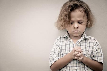 壁の近くに立って悲しい小さな男の子の肖像画 写真素材