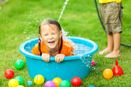 garden fountain: brother and sister playing with water near a house at the day time Stock Photo