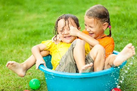 hose: hermano y hermana jugando con agua cerca de una casa en el tiempo del día Foto de archivo