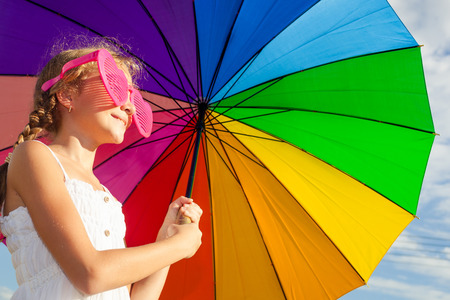 teen girl standing with umbrella on the blue sky background at the day time photo