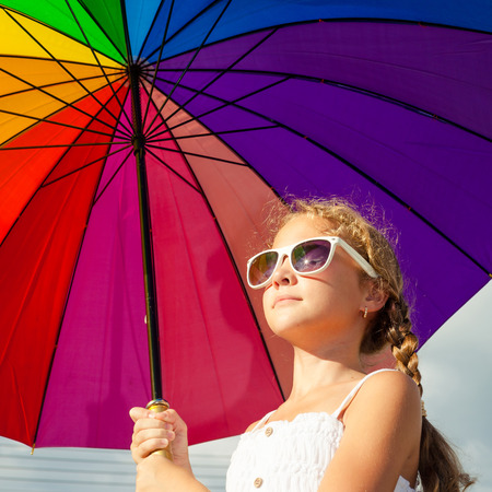teen girl standing with umbrella on the blue sky background at the day time