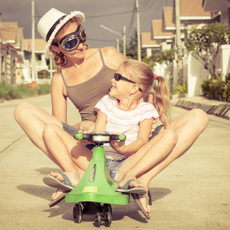 mother and little daughter playing near a house at the day time. Concept of friendly family. photo
