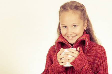sweater girl: portrait of a cute teen girl in red sweater holding a mug in his hands with hot tea