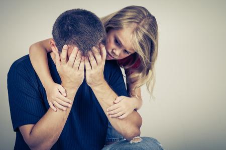 niños tristes: retrato de una hija triste que abraza a su padre Foto de archivo