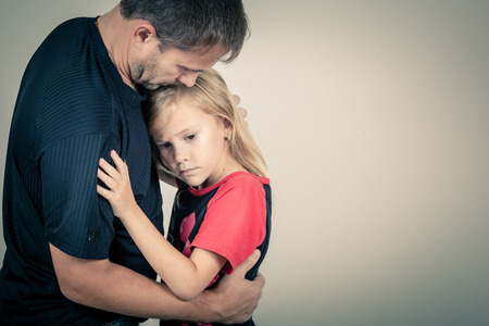 girl care: portrait of one sad daughter hugging her father
