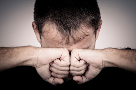 resentment: portrait one sad man standing near a wall and covers his face Stock Photo