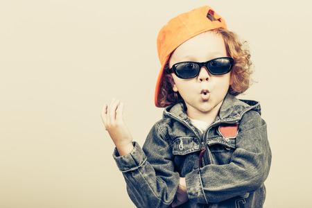 패션 아이. 행복 한 소년 모델입니다. 야구 세련된 어린 소년. 청바지 재킷에 잘 생긴 아이. 스톡 콘텐츠