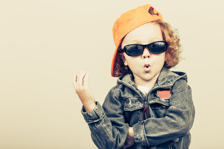 niño modelo: Moda infantil. Modelo de niño feliz. Niño pequeño con estilo en el béisbol. Chico guapo en la chaqueta de jeans. Foto de archivo