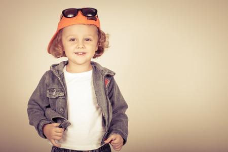 Fashion child. Happy boy model. Stylish little boy in baseball.  Handsome  kid  in the jeans jacket. photo
