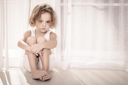 autism: Portrait of sad little boy sitting near the window Stock Photo