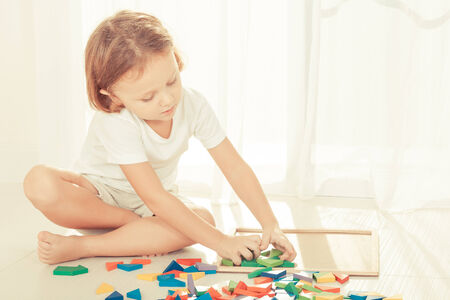 one room school house: little boy playing with wooden mosaic on the floor Stock Photo