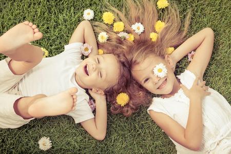 florecitas: Niño feliz y niña acostada en la hierba en el día. Concepto de un hermano y una hermana para siempre.