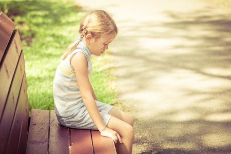Dzieci: Smutna dziewczynka siedzi na ławce w parku w czasie dnia Zdjęcie Seryjne