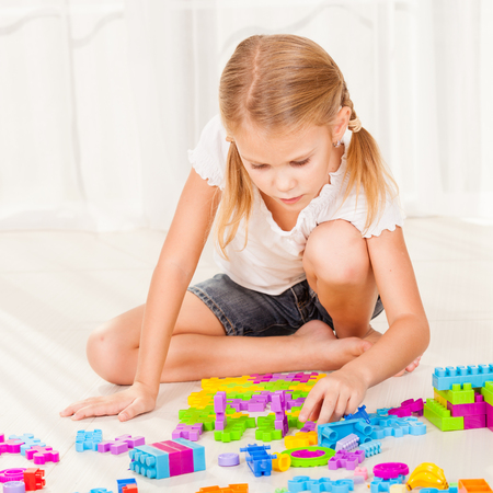 one room school house: Little girl playing on the floor at home Stock Photo