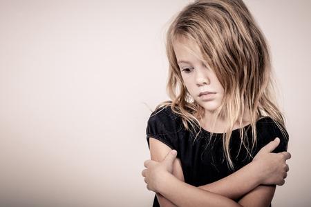 Portrait of sad blond little girl standing near wall