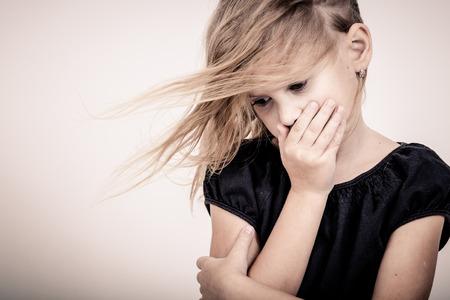 Portret van trieste blond meisje staande in de buurt muur