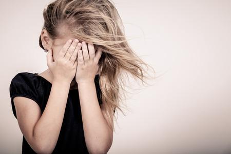 Portrait de triste blond petite fille debout près du mur Banque d'images