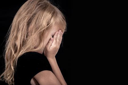 Portret van trieste blonde meisje staande in de buurt muur Stockfoto