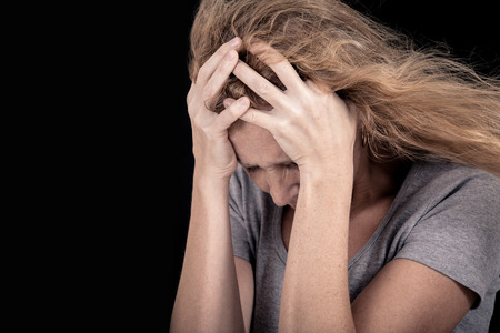 retrato de una mujer triste que se coloca cerca de una pared y sosteniendo su cabeza en sus manos Foto de archivo
