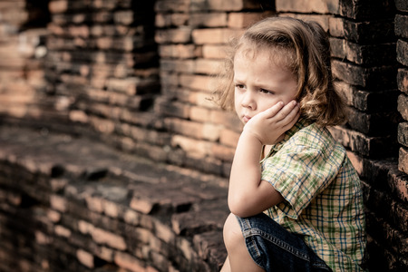anxiety: Portrait of sad little boy sitting near the wall at the day time