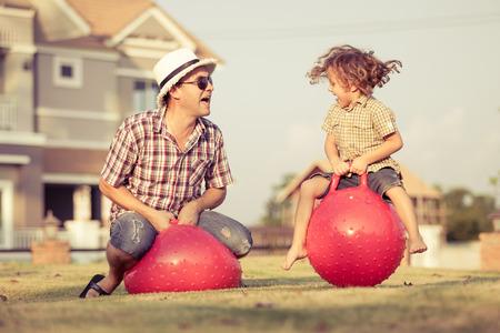 Vati und Sohn springt auf aufblasbare Bälle auf dem Rasen vor dem Haus an der Tageszeit Lizenzfreie Bilder