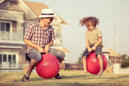 papa: Papa et fils sautant sur ballons gonflables sur la pelouse devant la maison au moment du jour