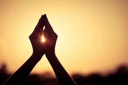 personas orando: silueta de manos de una mujer durante la puesta de sol