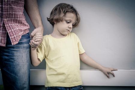 niños tristes: retrato de un hijo triste abrazando a su padre en el día