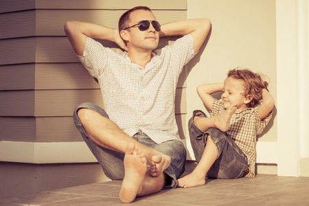 child couple: Dad and son playing near a house at the day time