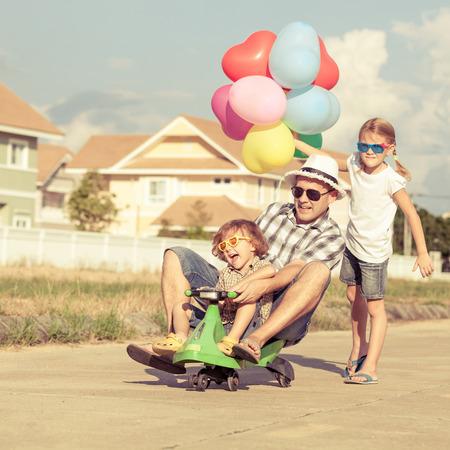 Vater und Kinder spielen in der Nähe eines Hauses an der Tageszeit Lizenzfreie Bilder