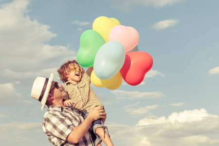 feeling: Dad and son playing with balloons near a house at the day time Stock Photo