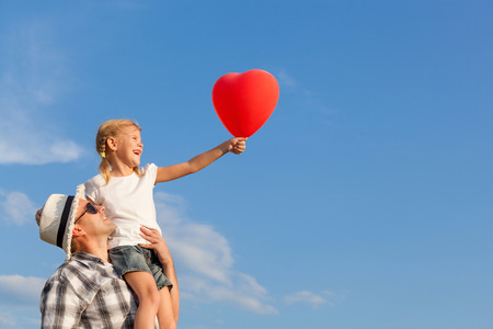Dad and daughter playing with balloon near a house at the day time Stock Photo