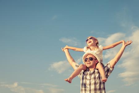 Papá e hija jugando cerca de una casa en el tiempo del día