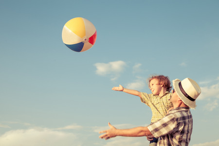 fun in the sun: Dad and son playing with balloon near a house at the day time Stock Photo