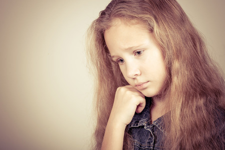 family relationships: Portrait of sad blond teen girl standing near wall Stock Photo