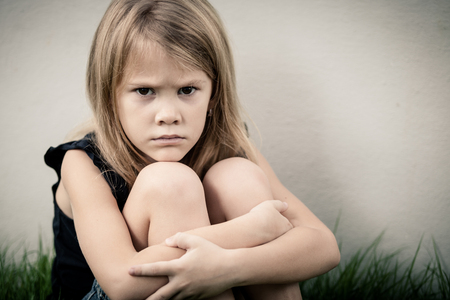 resentment: Portrait of sad blond little girl sitting near wall on outdoors
