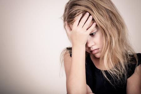 立っている悲しい金髪少女の肖像画付近の壁と手で顔をカバー