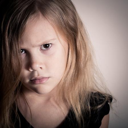 Portrét smutné blond holčička stojící u zdi