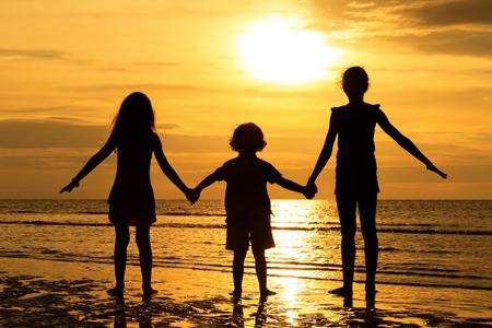 Glückliche Kinder spielen am Strand in den Sonnenuntergang Zeit