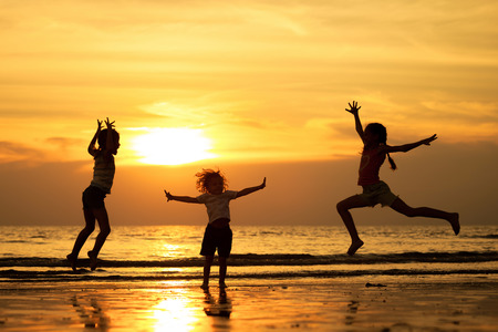 Happy children playing on the beach at the sunset time